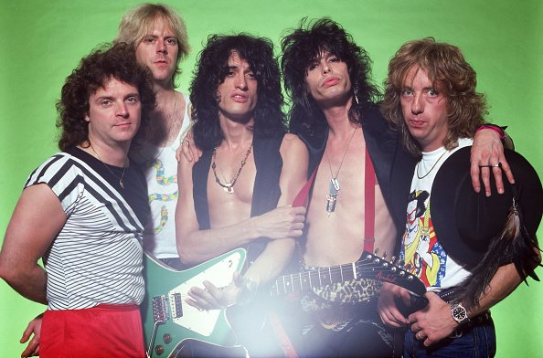 Brad Whitford, Joe Perry, Joey Kramer, Tom Hamilton, and Steven Tyler of Aerosmith pose for a portrait on July 11, 1984 at Pine Knob Music Center in Clarkston, Michigan. | Photo: Getty Images