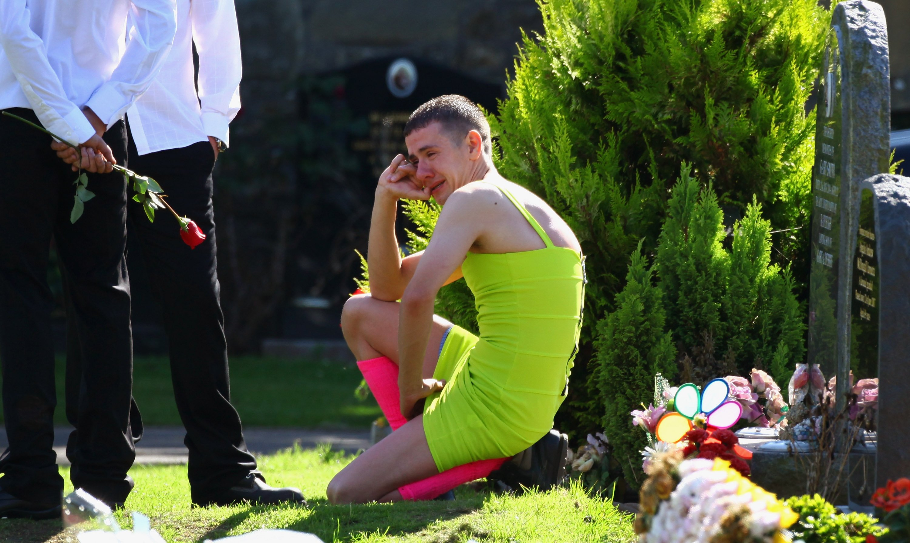 Barry Delaney wearing the lime-green dress, weeping as mourners gather at Barnhill Cemetery for the funeral of  Kevin Elliot in Dundee, Scotland | Photo: Jeff J Mitchell/Getty Images