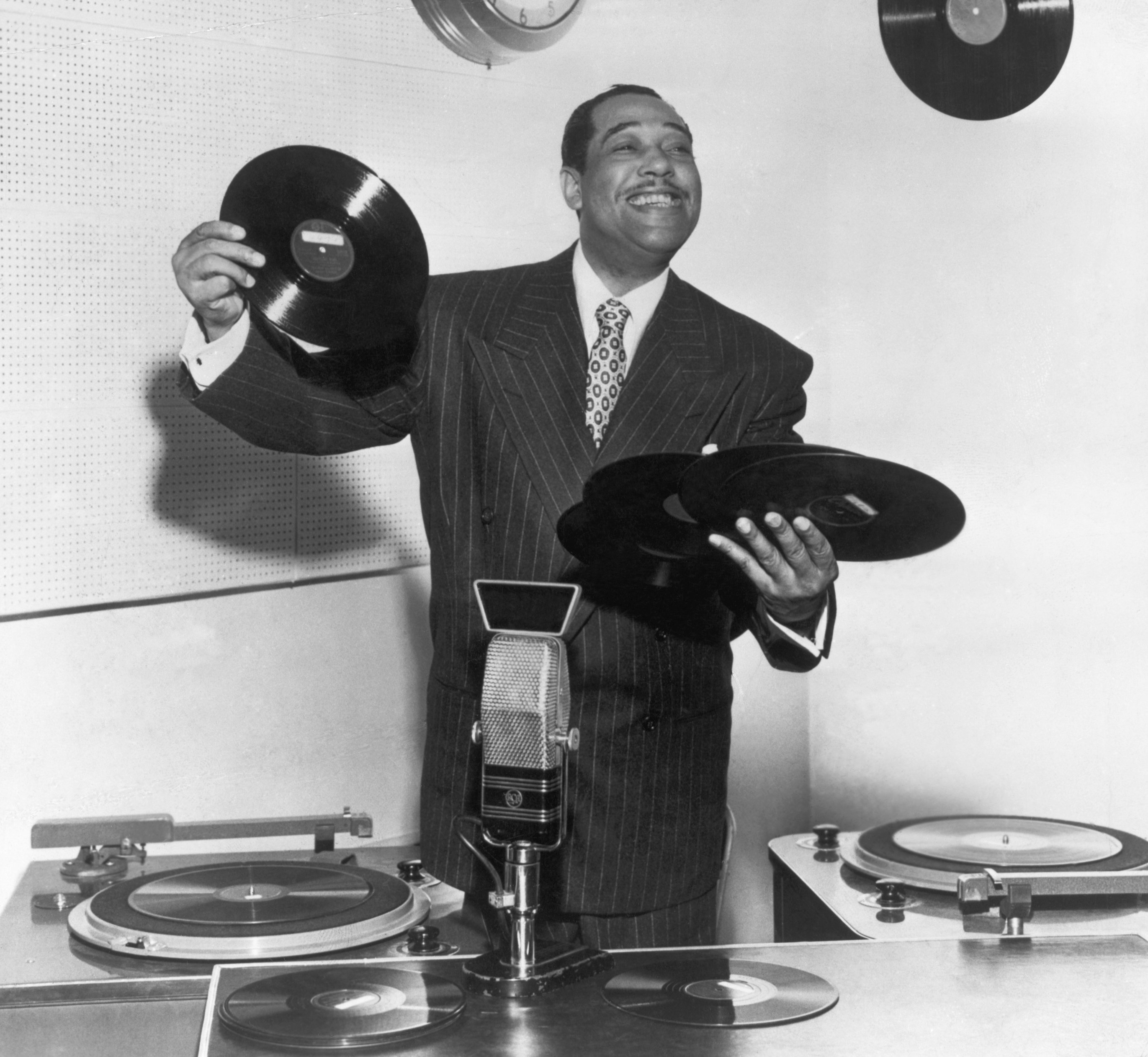 Duke Ellington (1889-1974), bandleader, composer and arranger, has his hands full as he tries role of disc jockey | Photo: Getty Images