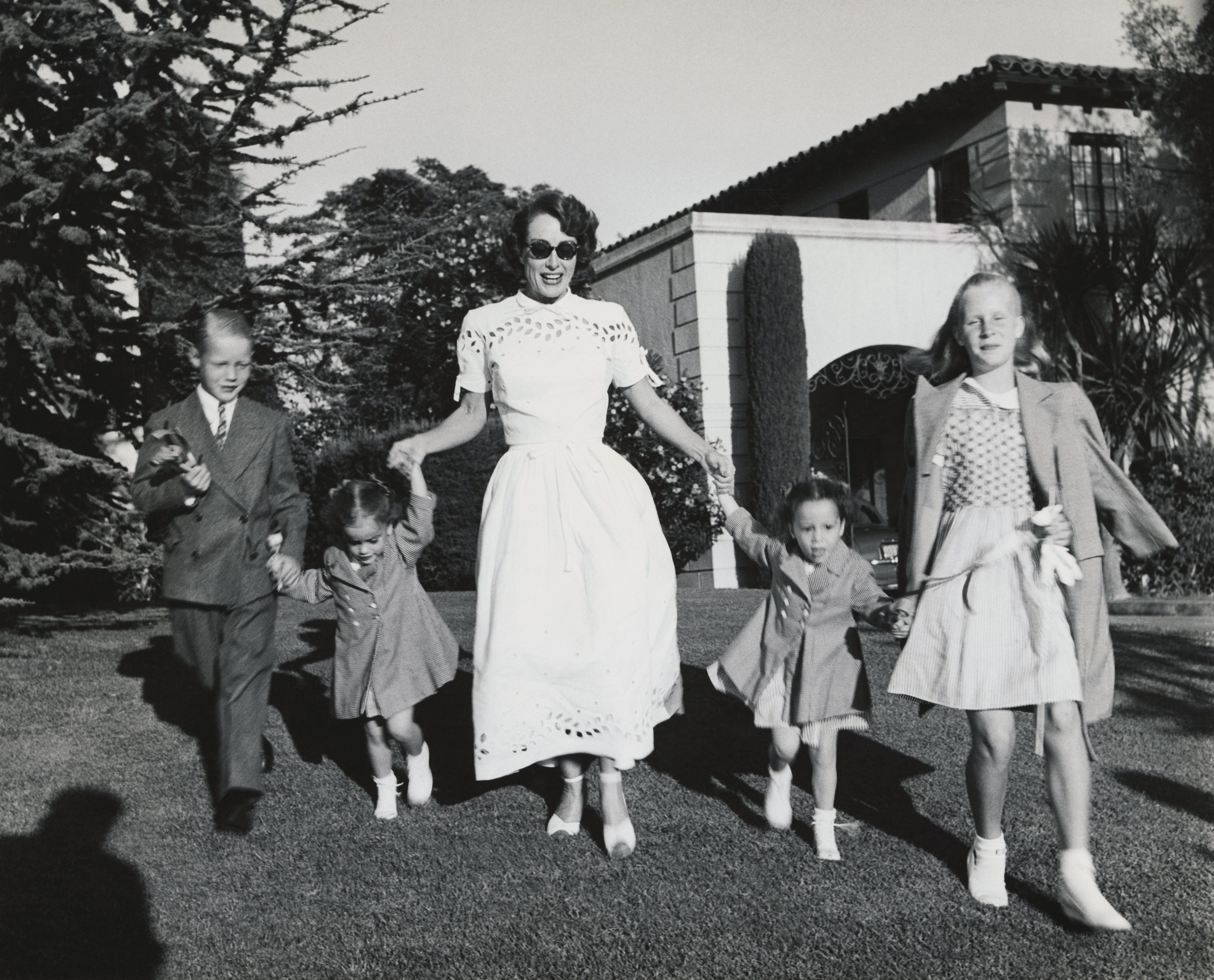 Joan Crawford and four children, Christopher, Cathy, Cynthia, and Christina romp on lawn following party given by Ann Rutherford for daughter Gloria's 5th birthday.   Source: Getty Images