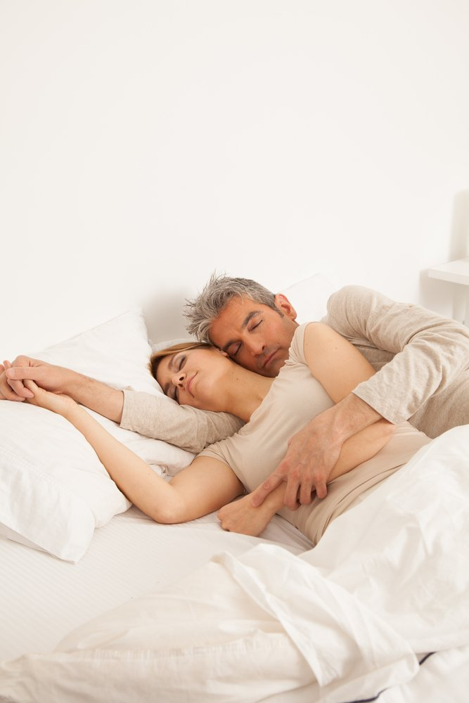 Elderly couple resting together in bed | Shutterstock