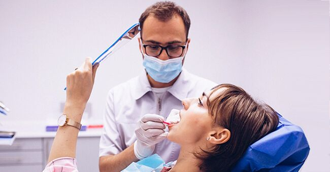 Daily Joke: A Woman and Her Husband Visit a Dentist during Their Vacation