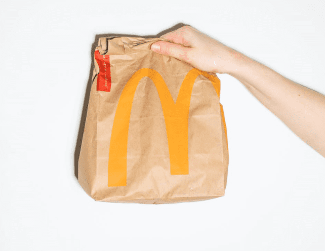 A person holds up a brown takeaway bag from McDonalds | Photo: Pexels/Polina Tankilevitch
