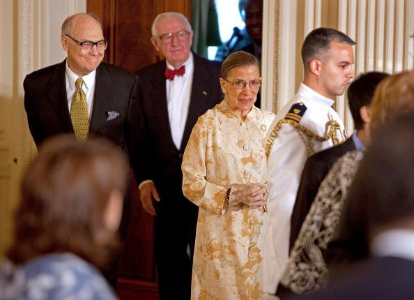 U.S. Supreme Court Associate Justice Ruth Bader Ginsburg (C) with Associate Justice John Paul Stevens (2nd L) during a reception for new Supreme Court Associate Justice Sonia Sotomayor in the East Room of the White House August 12, 2009, in Washington, DC. | Source: Getty Images.