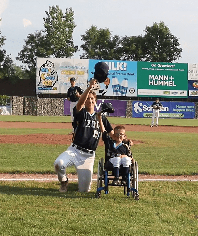 Brenden Lowery and a player for the baseball team Kalamazoo Growlers tip their caps off for the crowd. │Source: Facebook/kzoogrowlers