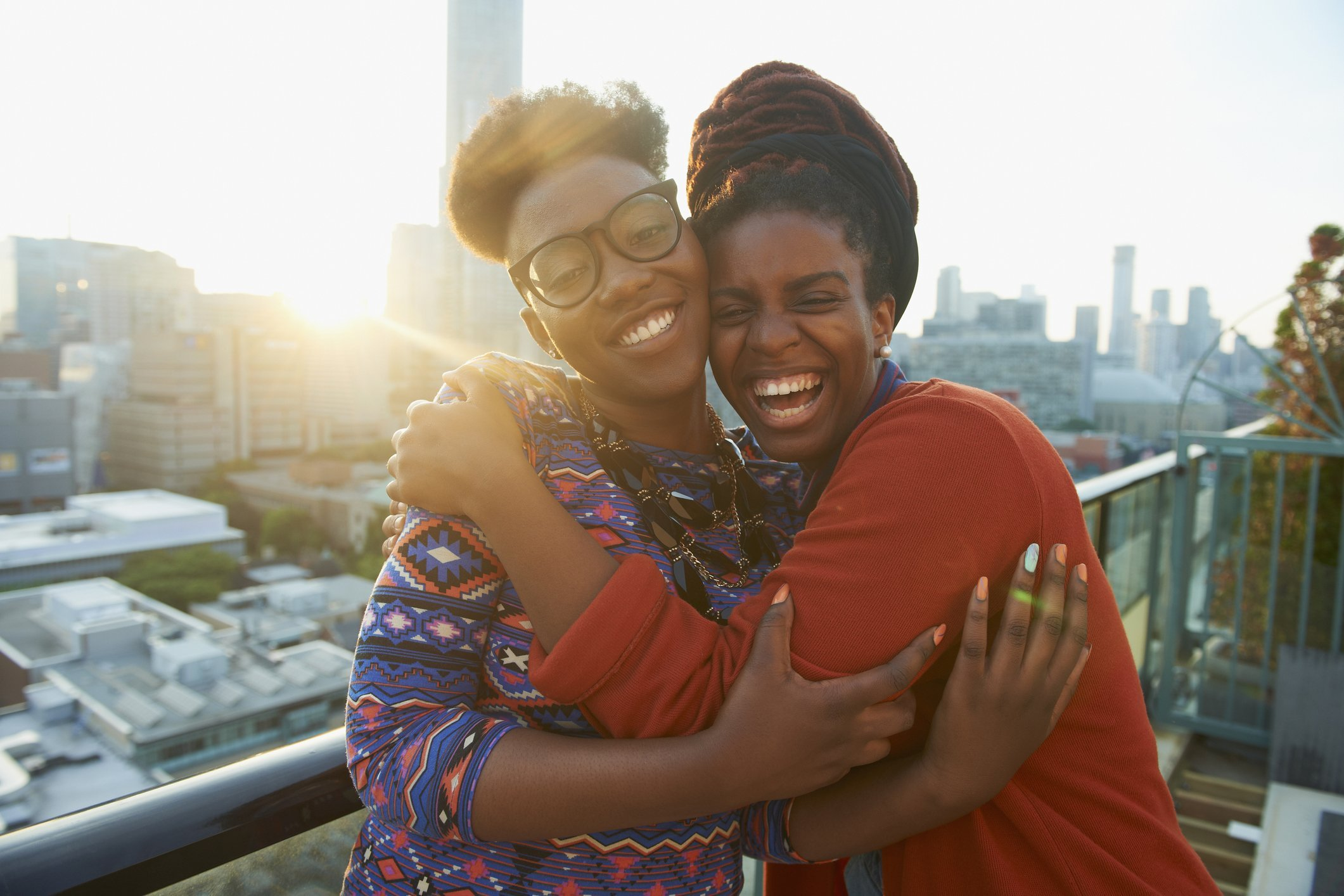 Sisters hugging on a rooftop in the city. | Photo: Getty Images
