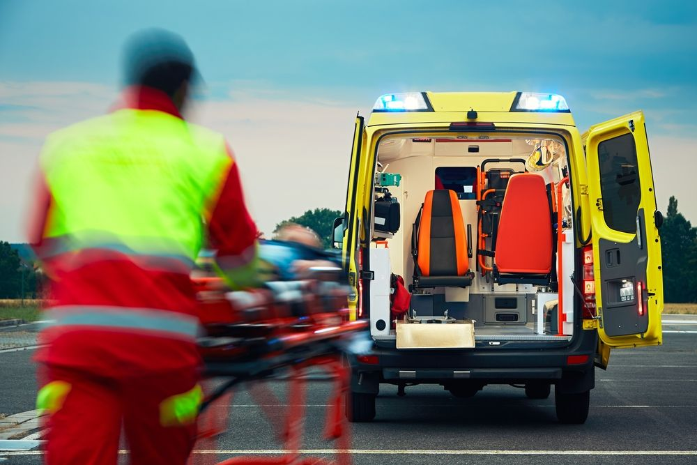 Paramedic pulling a stretcher with a patient to the ambulance.   Source: Shutterstock