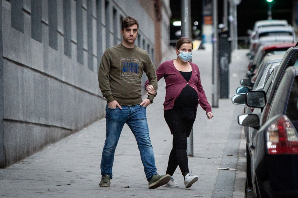 A young pregnant woman crossing the road with her spouse. | Photo: Getty Images