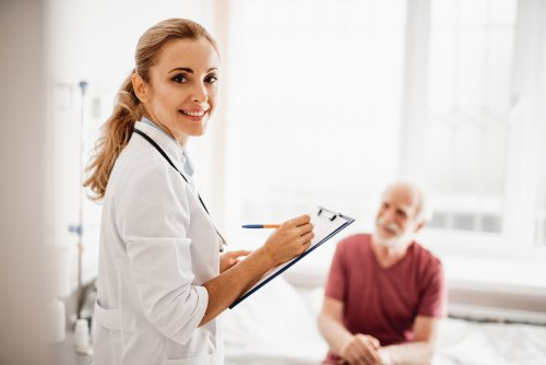 Lady in white lab coat holding clipboard and an elderly man sitting on the bed. | Source: Shutterstock