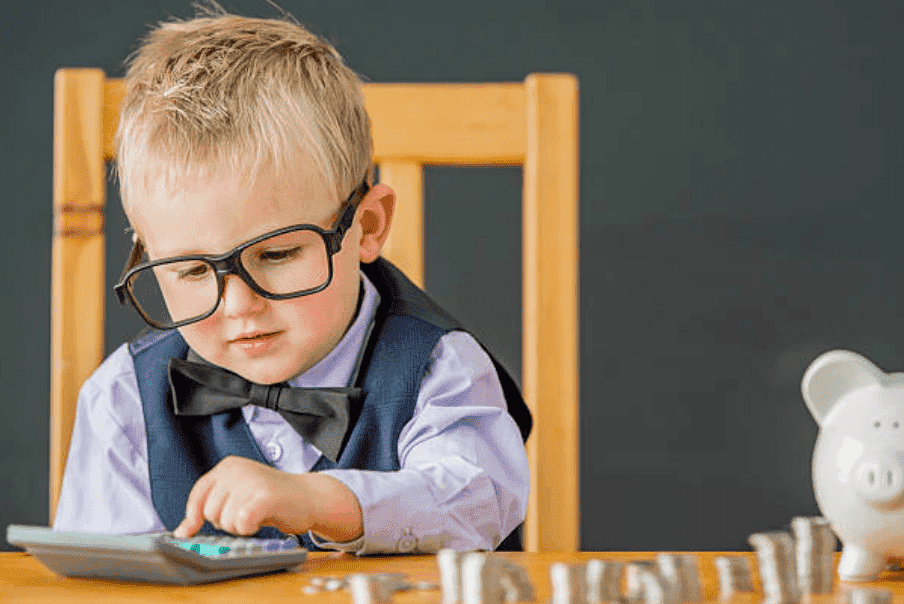 Little boy wearing glasses and a bow tie count's coins for his piggy bank using a calculator | Source: Getty Images
