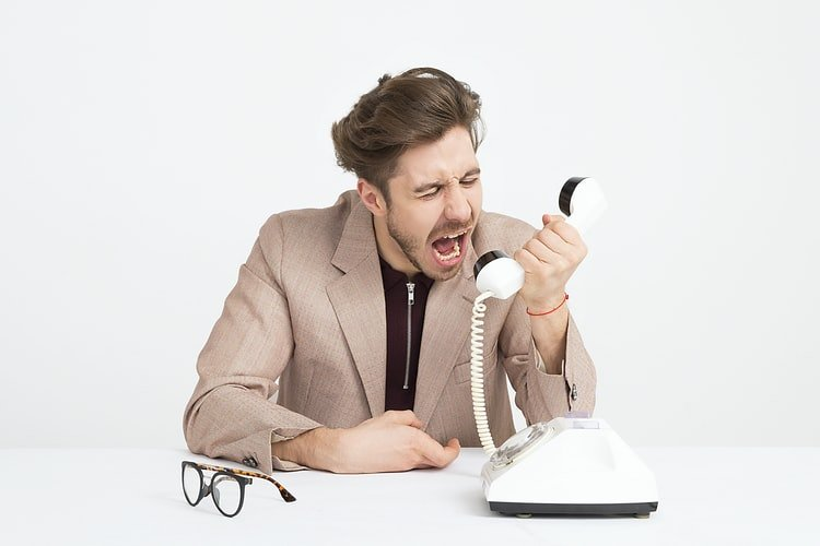 A man angrily answering the phone.   Photo: Unsplash.