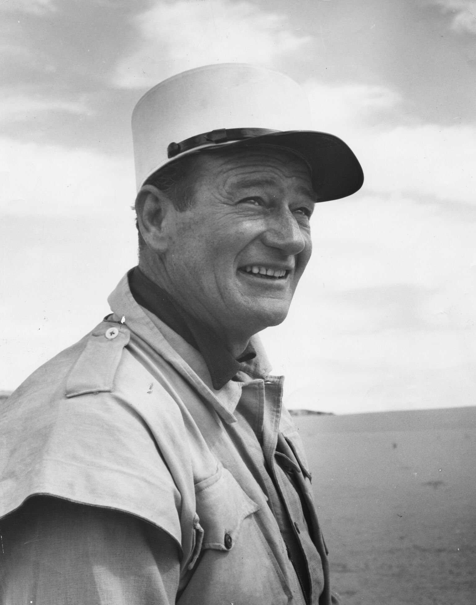 """John Wayne in costume, standing in a desert landscape filming the movie """"Legend of the Lost"""" 