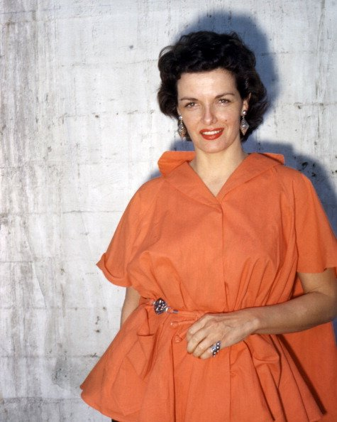 Photo of Jane Russell wearing an orange dress, with large drop earrings, in a studio portrait, against a white background, circa 1955. | Photo: Getty Images