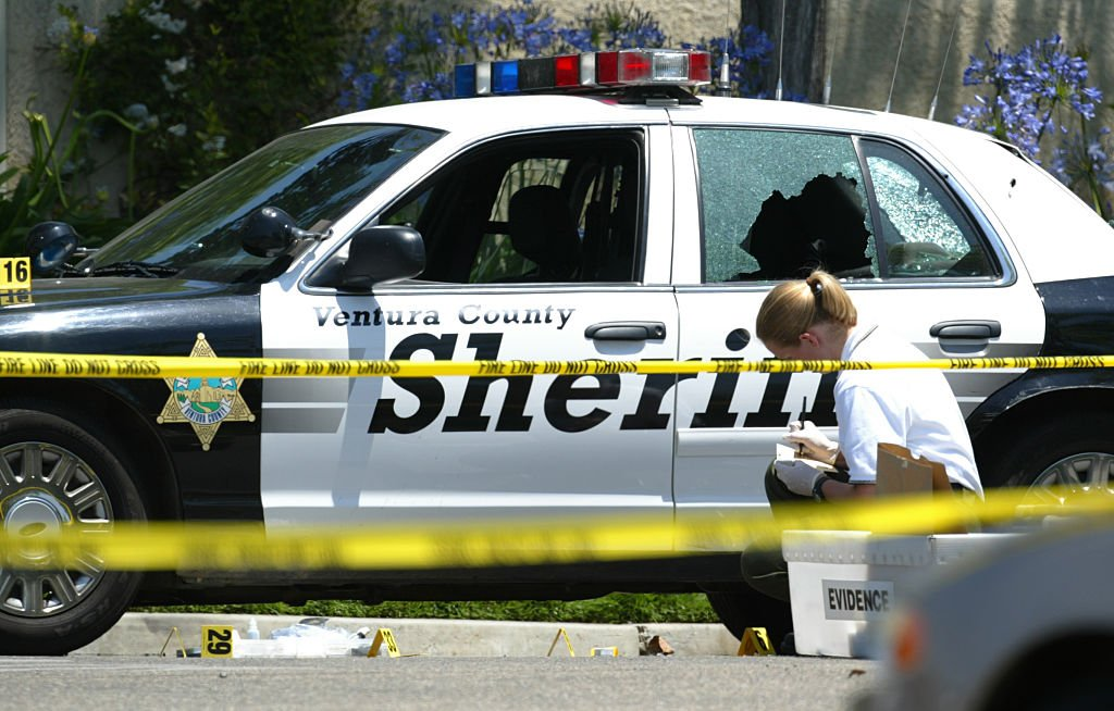 A Crime scene investigator examines a bullet hole in the side of a patrol car that in which a deputy was shot on May 31, 2005   Photo: Getty Images