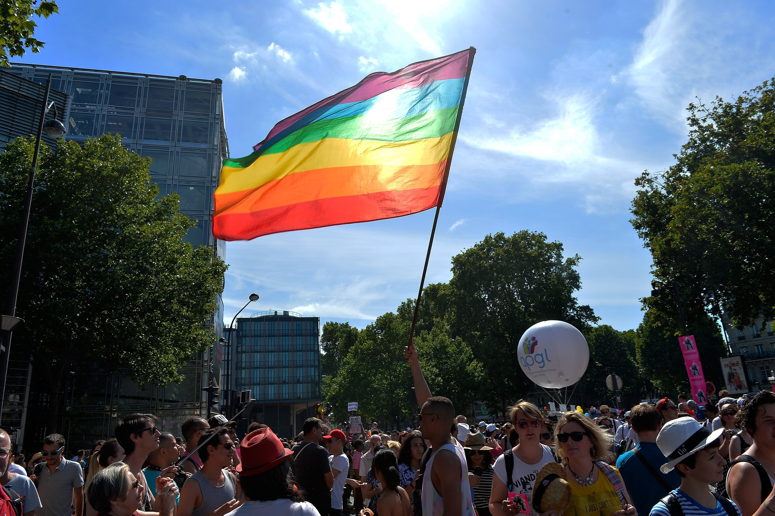 A rainbow flag being waved at the Gay Pride Parade in Paris | Photo: Getty Images