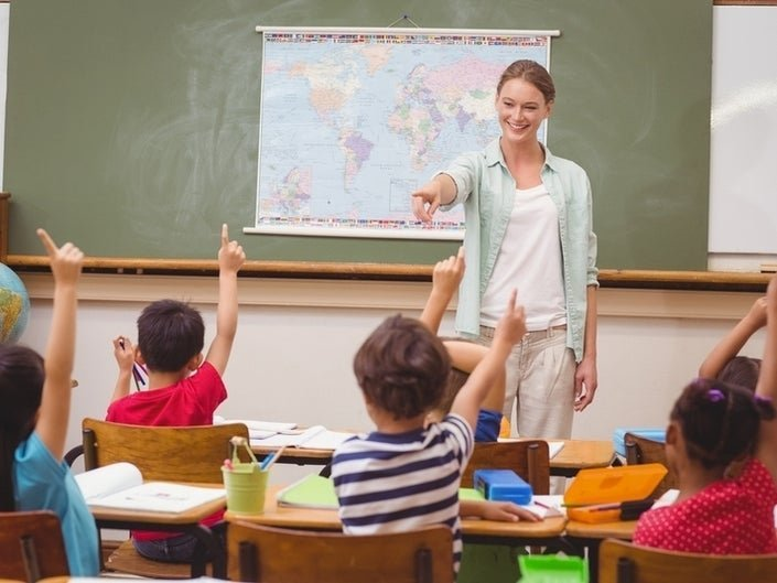 Happy elementary teacher aiming at school kids to answer her question | Photo: Shutterstock