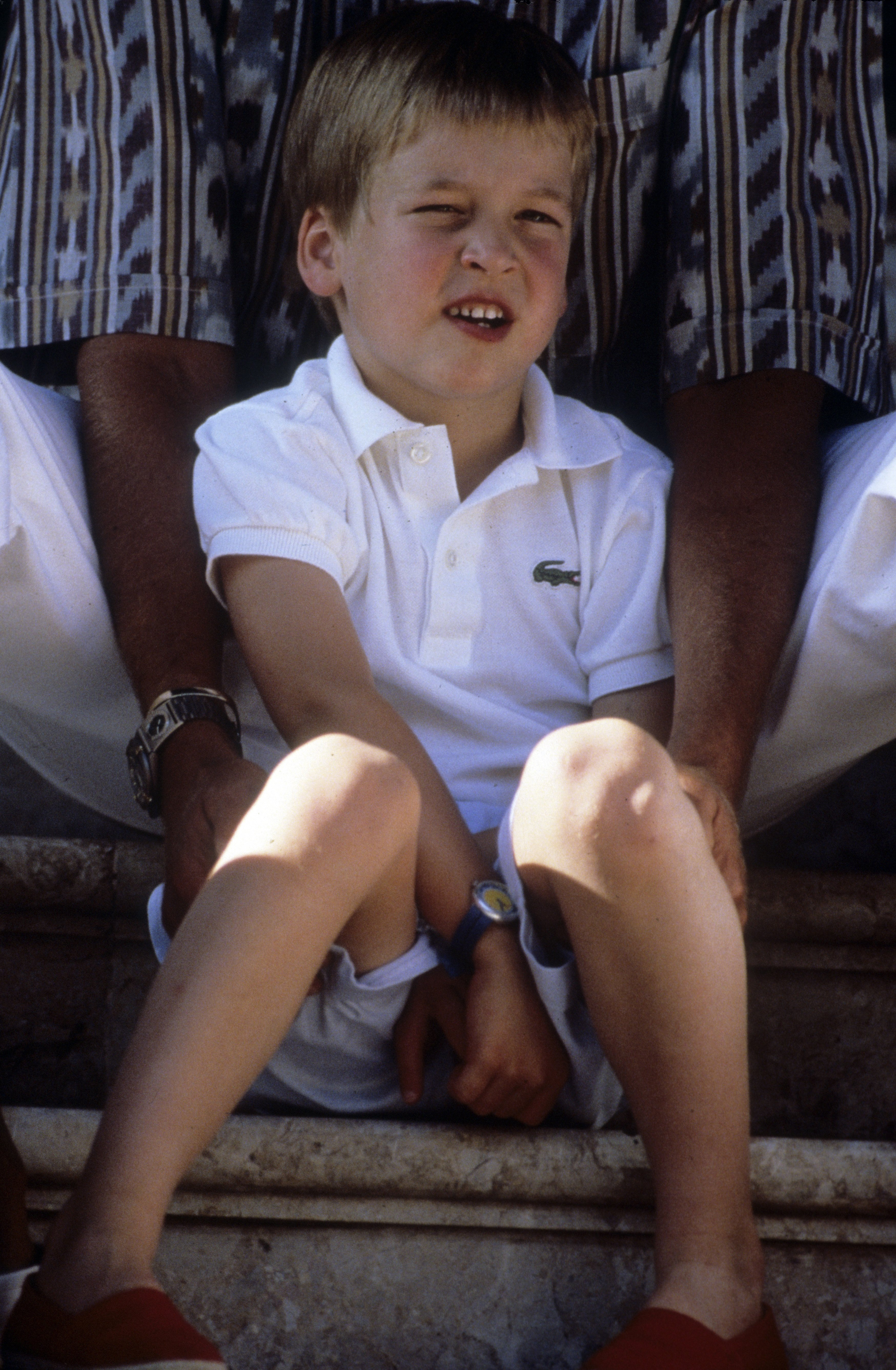 Prince William sits with King Juan Carlos during a summer holiday in Majorca on August 13, 1988, in Palma, Spain. | Source: Getty Images.