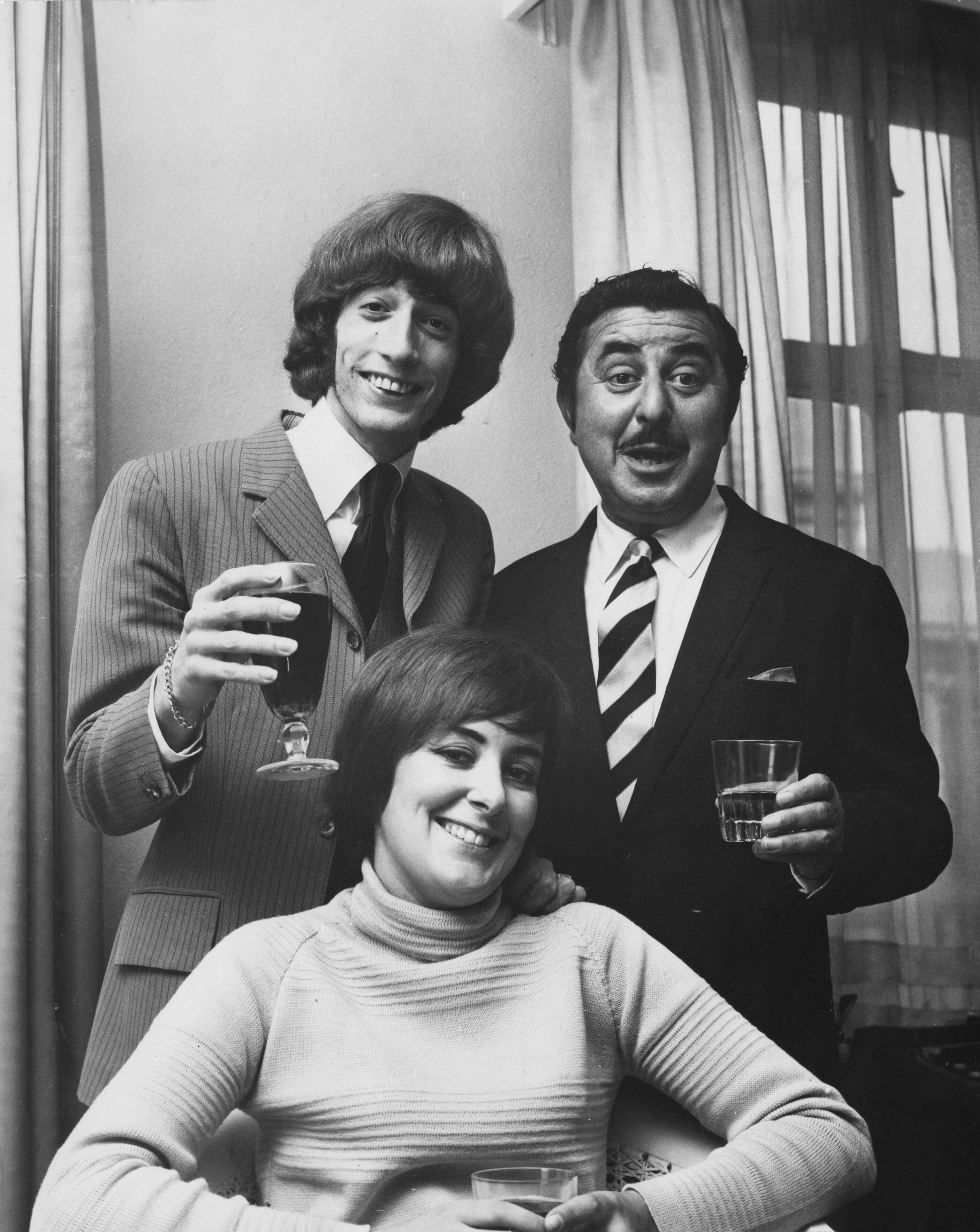 Robin Gibb with his first wife, Molly, and managing director of NEMS Enterprises, Vic Lewis, celebrating Gibb's signing of a contract with NEMS, 5th September 1969.   Source: Getty Images