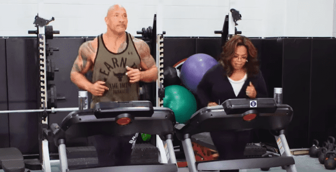 Dwayne Johnson and Oprah running the treadmill in their new 2020 Weight Watchers commercial. | Source: YouTube/WW formerly Weight Watchers.