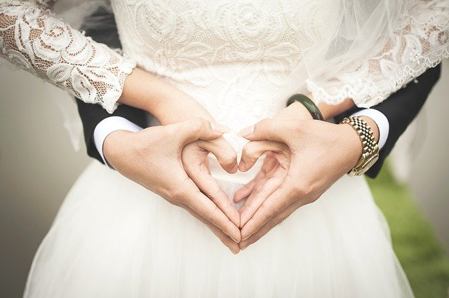 A bride and groom create a heart with their hands | Photo: Pixabay