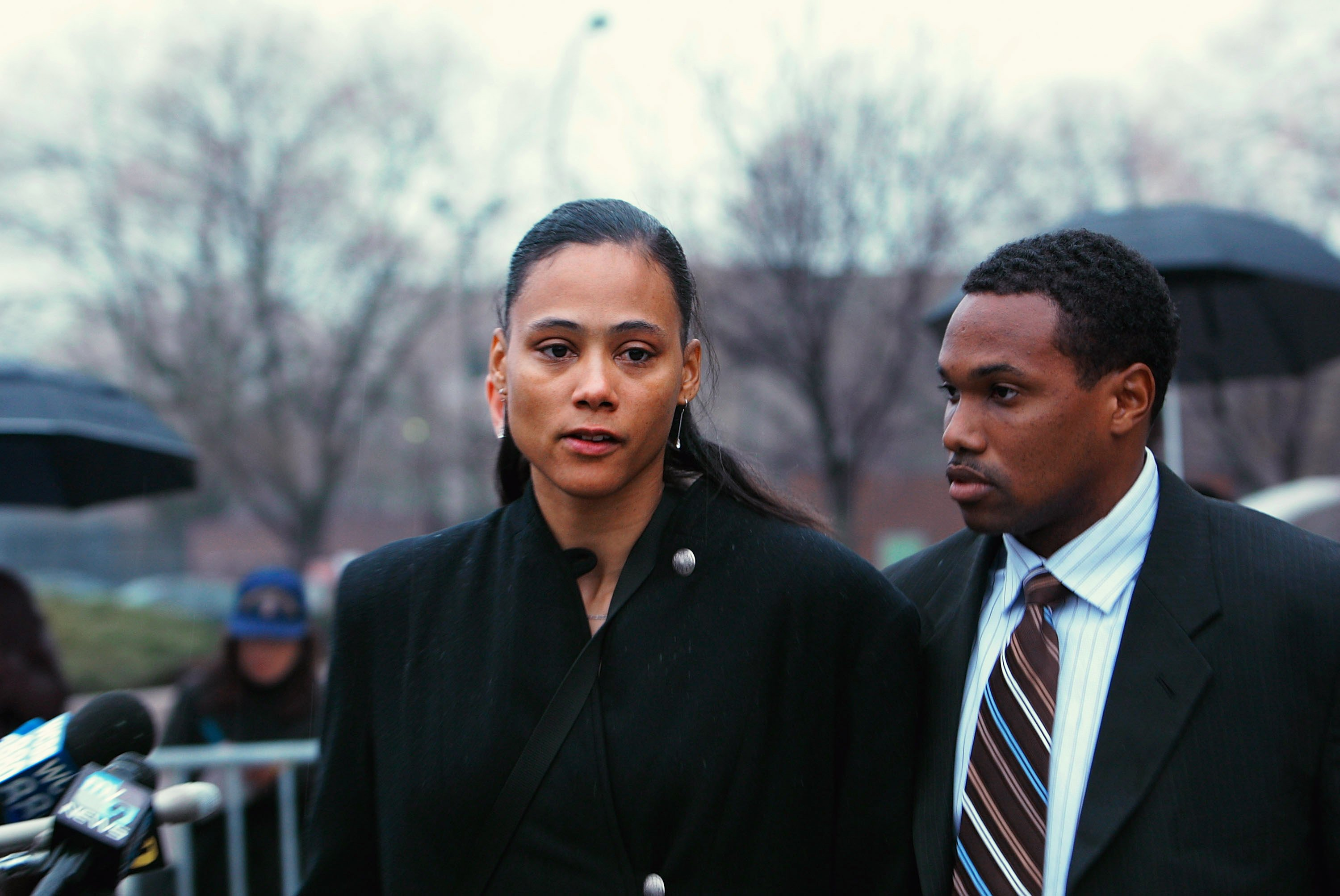 Marion Jones stands with her husband Obadele Thompson after she leaves court on January 11, 2008, in White Plains, New York | Photo: Chris Hondros/Getty Images