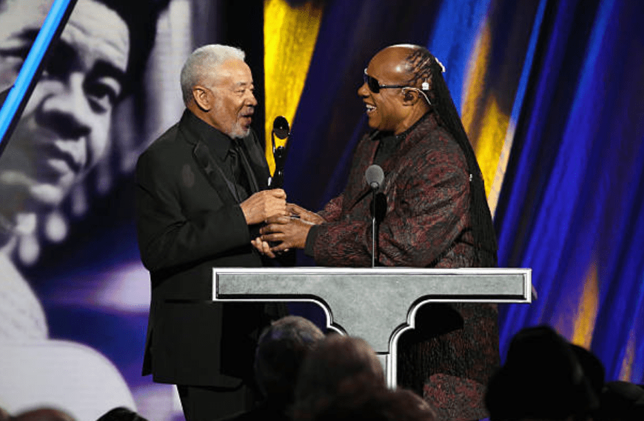Stevie Wonder hand an award to Bill Withers during the ceremony at the 30th Rock And Roll Hall Of Fame Induction Ceremony on April 18, 2015, in Cleveland, Ohio | Source: Getty Images (Photo by Kevin Kane/WireImage for Rock and Roll Hall of Fame)