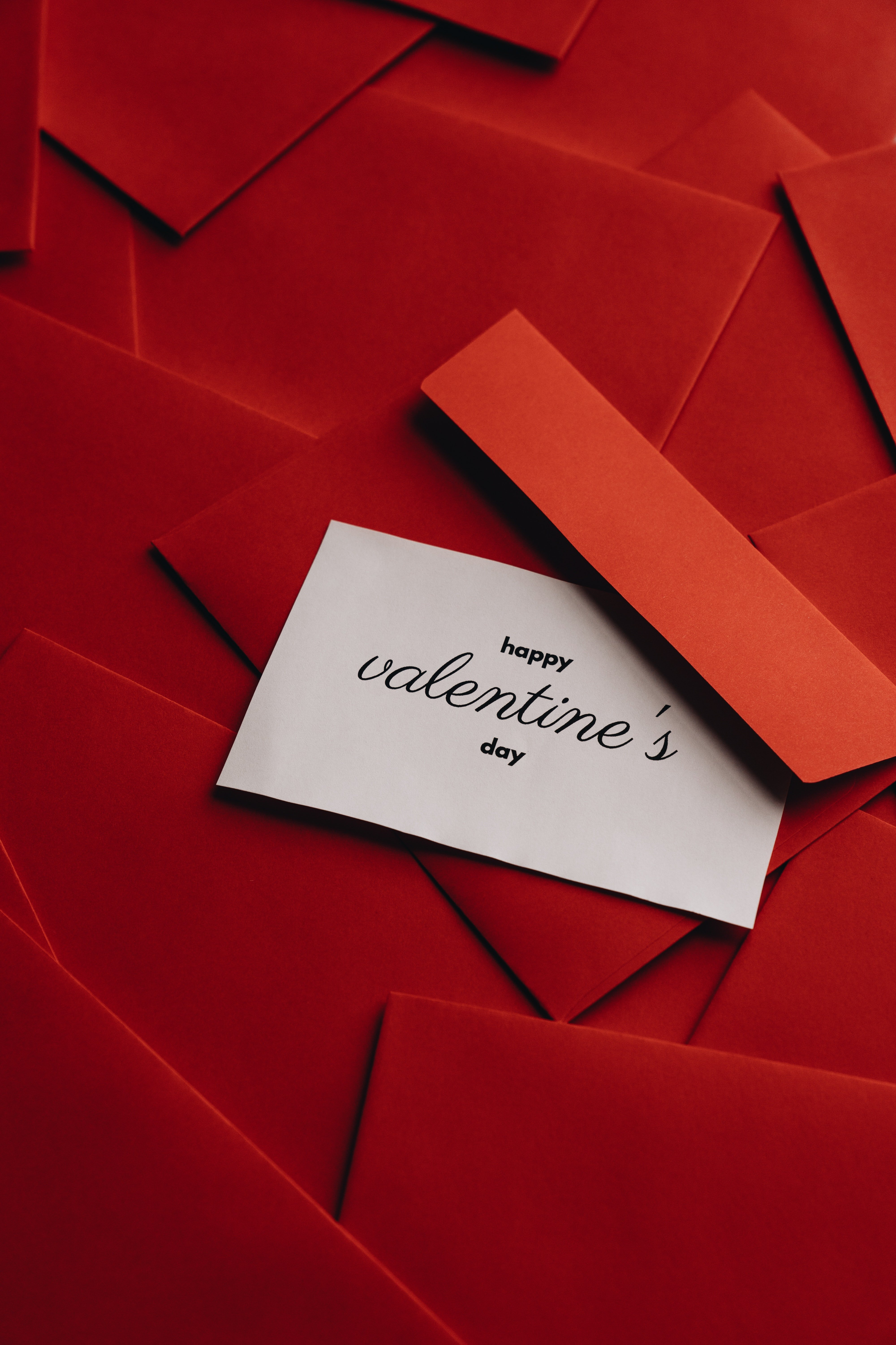 A white Valentine's note ontop of red envelopes.   Photo: Pexels.