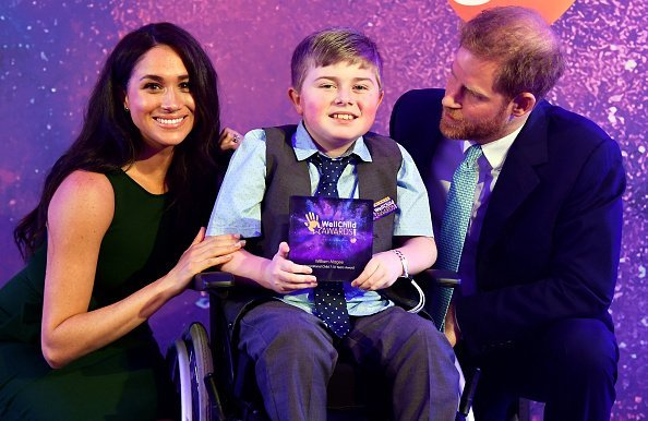 Prince Harry, Duke of Sussex and Meghan, Duchess of Sussex pose for a photograph with award winner William Magee during the WellChild Awards | Photo: Getty Images