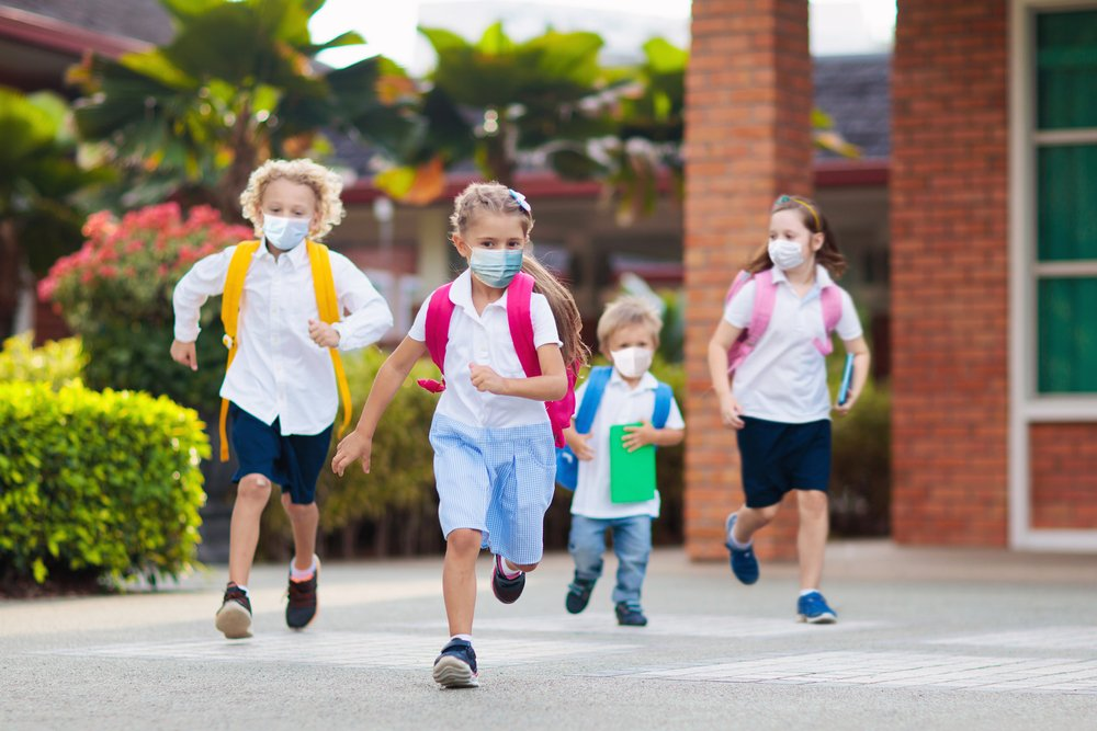 School children wearing face masks during the COVID-19 pandemic and running as they play together | Photo: Shutterstock/ FamVeld