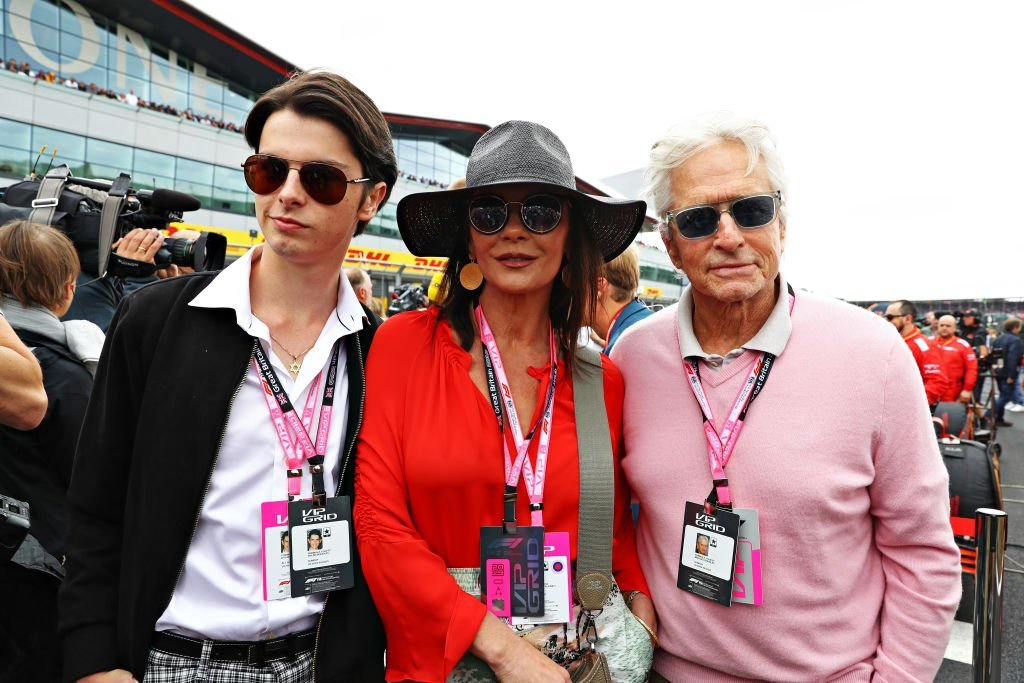 Actors Michael Douglas and Catherine Zeta-Jones and their son Dylan Douglas pose for a photo on the grid before the F1 Grand Prix of Great Britain at Silverstone | Photo: Getty Images