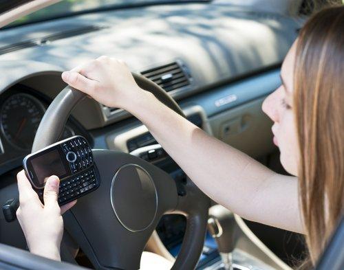 Une adolescente qui envoie des SMS et conduit. | Source : Shutterstock