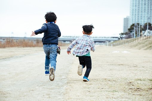Photo of two young boys running across a field | Photo: Getty Images