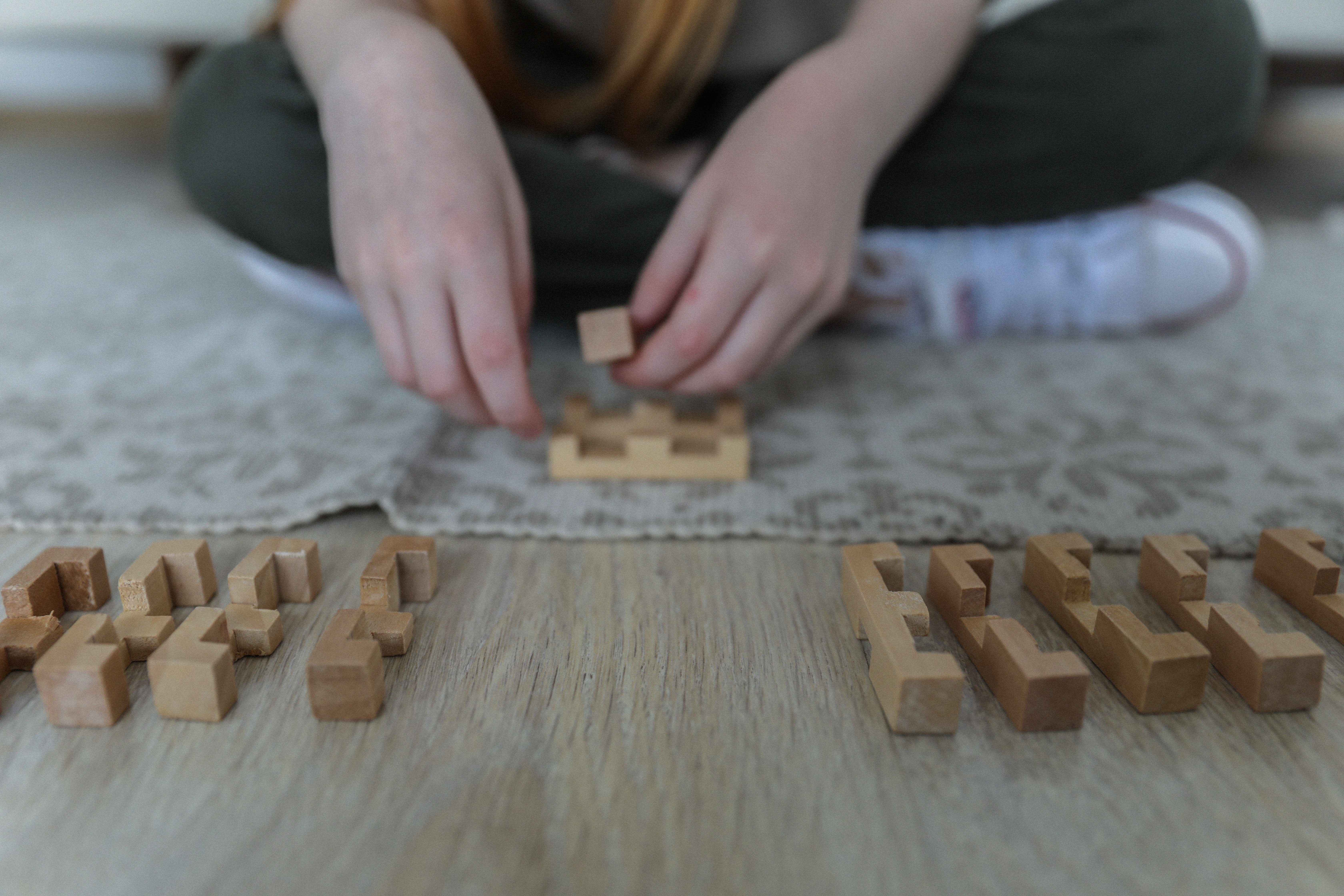 A girl attempts to make sense of wooden puzzle blocks laid out in front of her   Photo: Pexels/Monstera