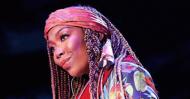 Brandy Turns Heads Posing in Blue and Pink Print Suit & Beret Showing Her Long Braids in Photo