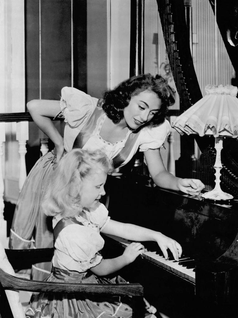 Joan Crawford helping her daughter Christina during her piano lesson in the United States on July 25, 1947   Photo: Getty Images