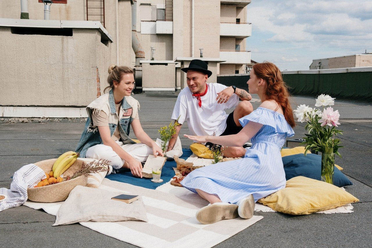 Three friends having a rooftop picnic. | Source: Pexels/cottonbro