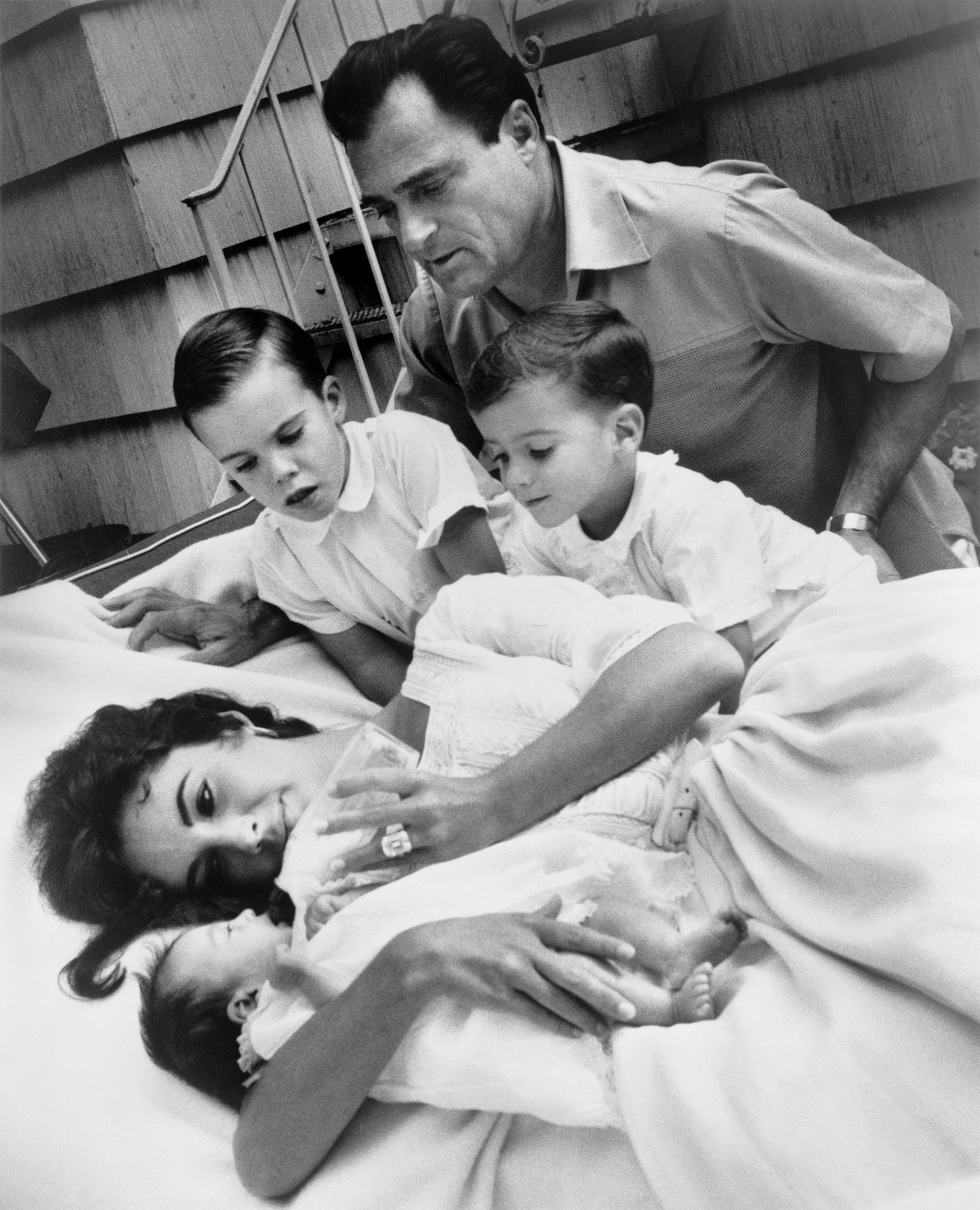 Elizabeth Taylor bottle-feeding newborn Liza Todd with her sons Christopher and Michael H. Wilding, and her husband Michael Todd observing, 1957| Photograph by Toni Frissell. Wikimedia Commons Images