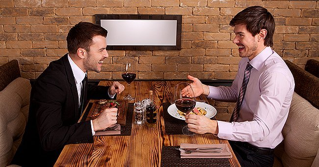 Two friends at a dinner enjoying a nice meal while having a conversation | Photo: Shutterstock