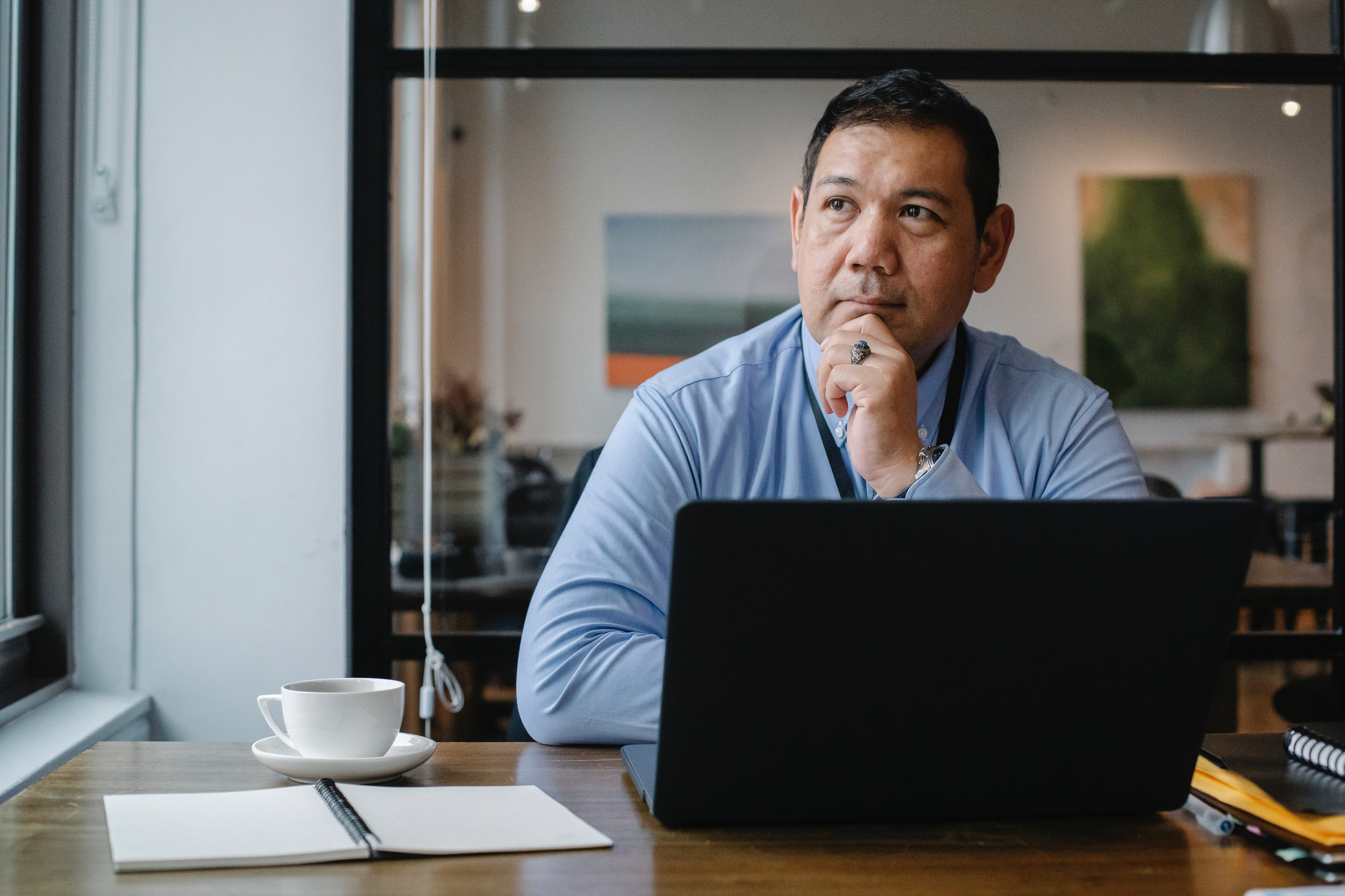 Man behind his office desk staring out the window | Source: Pexels