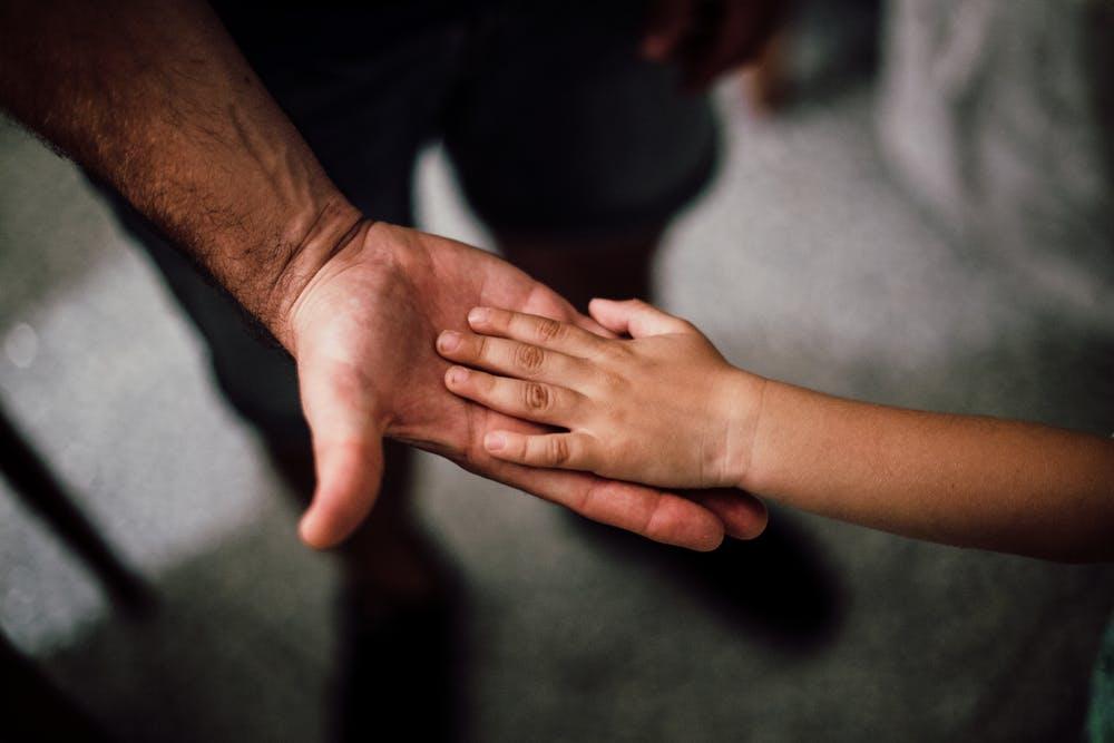 Vater hält Hand eines Kindes - Foto: Pexels