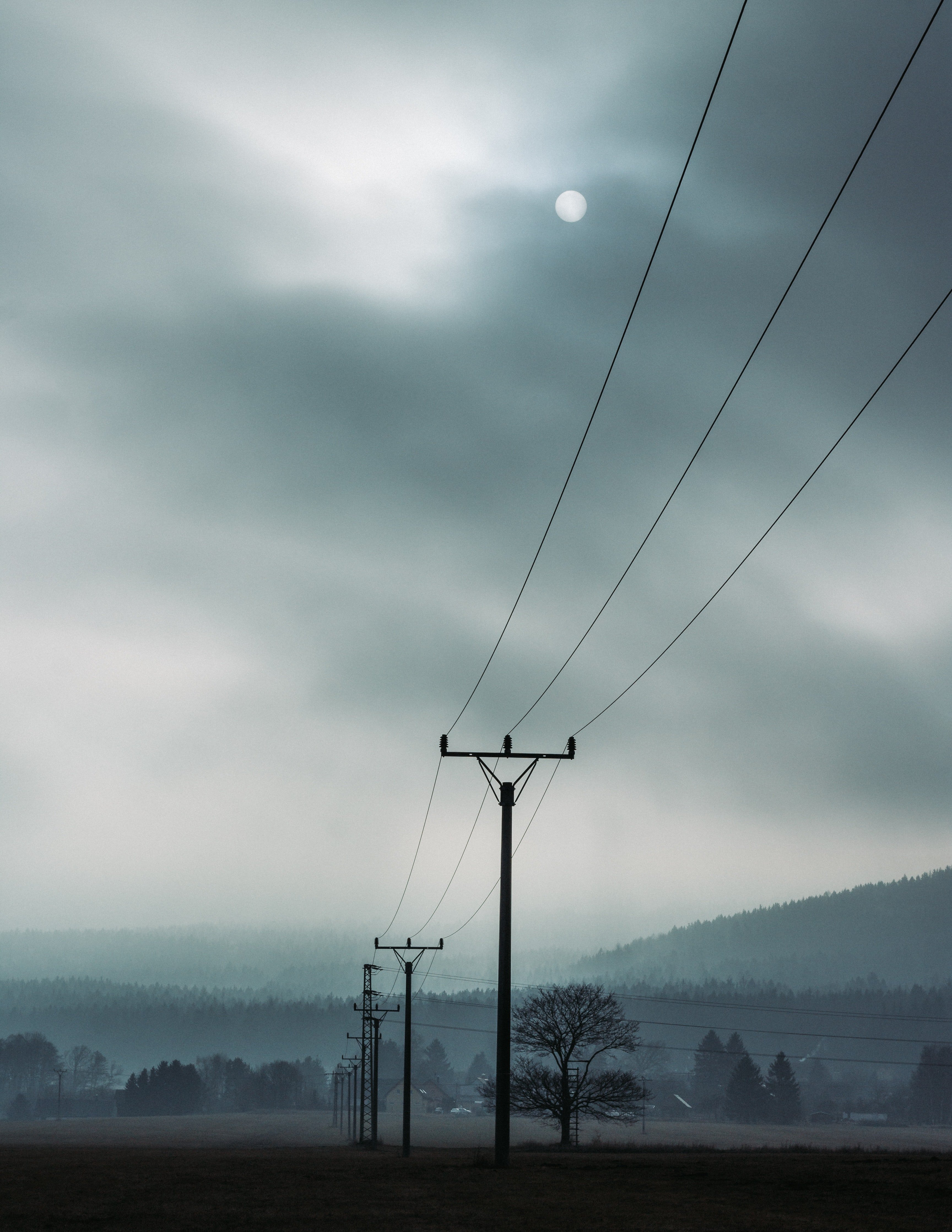 Landscape picture of electric posts on a cloudy day. | Source: Pexels.