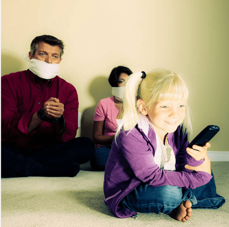 Little blonde girl smiles holding the remote and watching television, while her parents a tied up behind her | Source: Getty Images