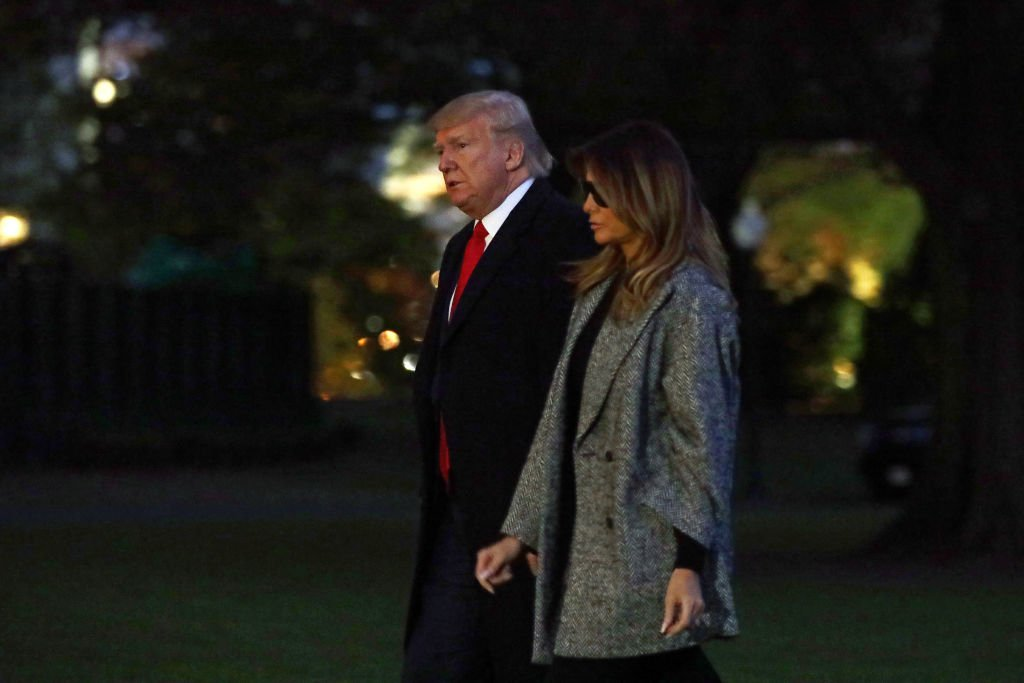 President Donald Trump and first lady Melania Trump walk on the South Lawn after they returned to the White House | Photo: Getty Images