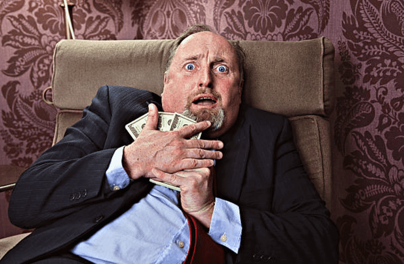 Frightened man sitting on a couch holds onto his money tightly | Source: Getty Images