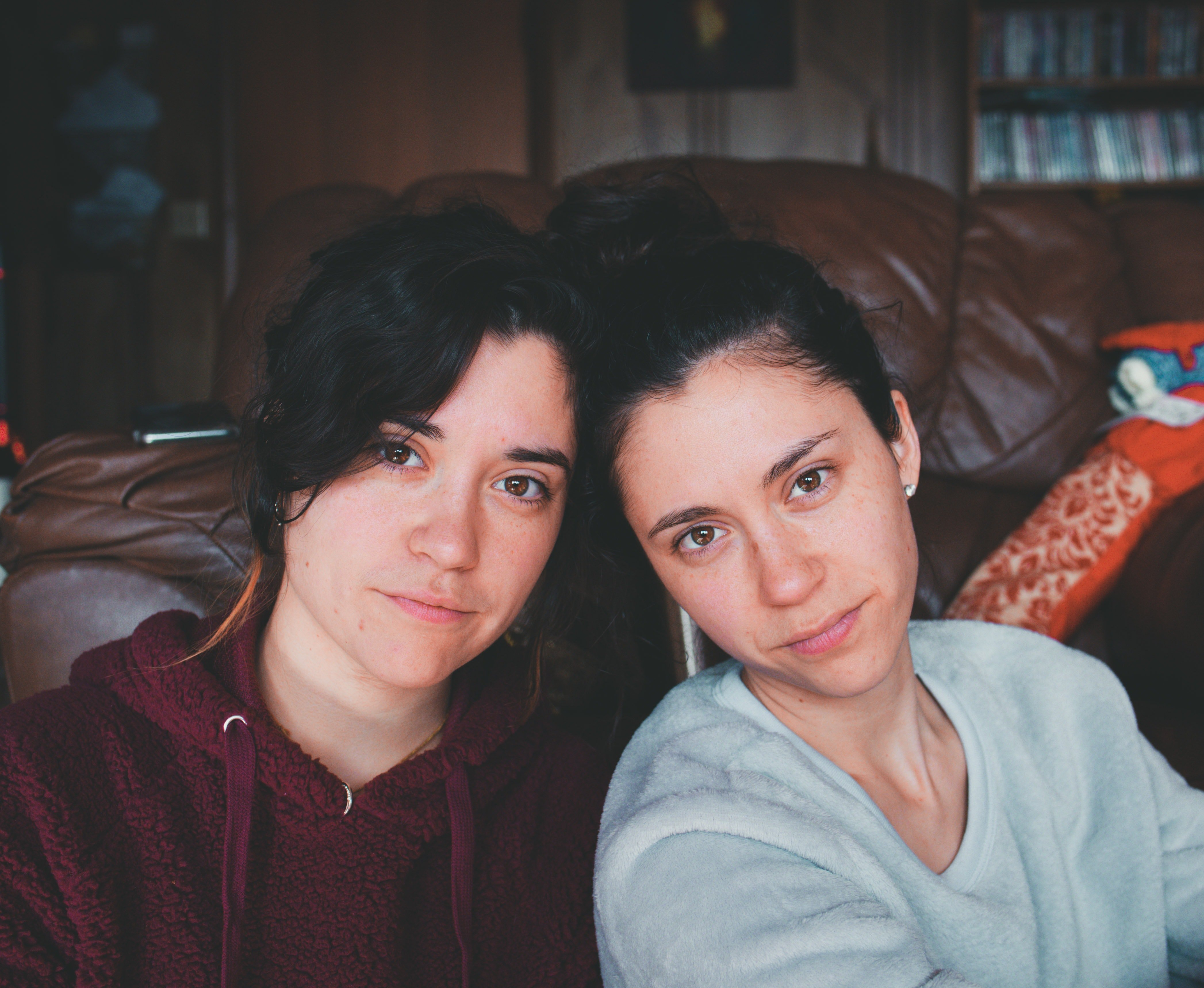 Twin sisters take a picture of themselves in the living room   Photo: Pexels