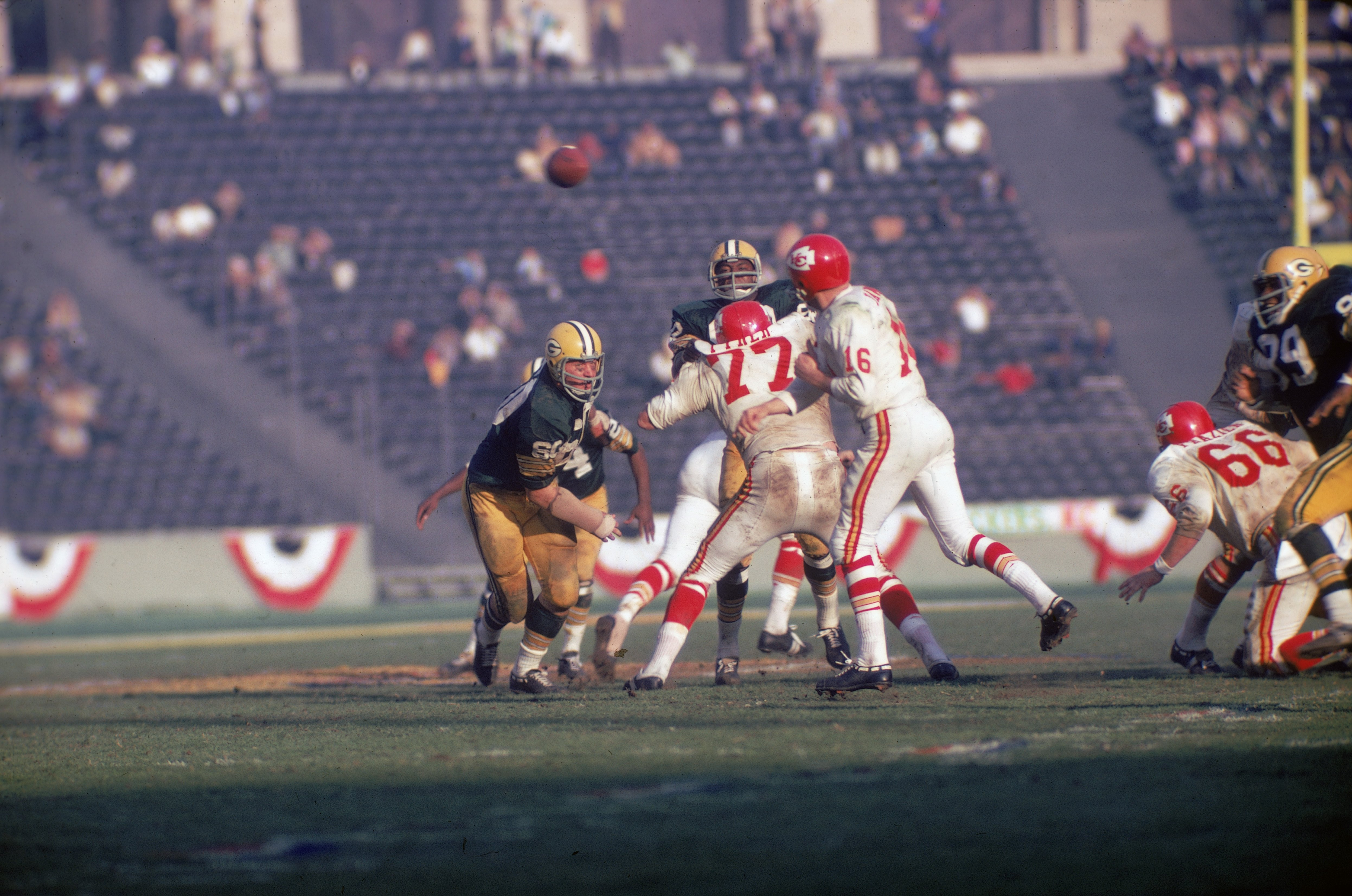 Football player Len Dawson (center, #16 in white), quarterback for the Kansas City Chiefs, throws the ball as opponent Lee Roy Coffey (left, #80) closes in during the Super Bowl, Los Angeles, California, January 15, 1967 | Photo: Getty Images