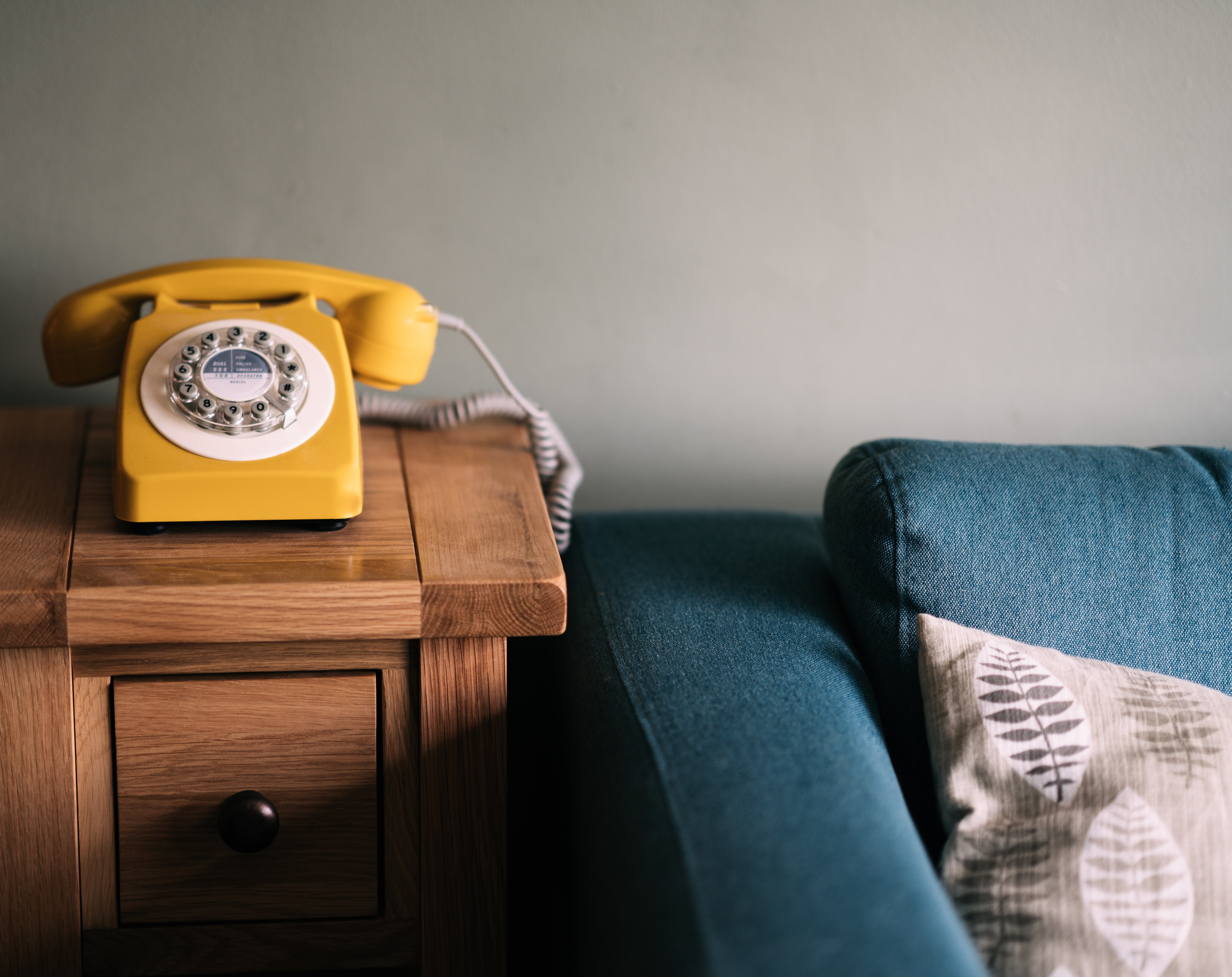 A yellow telephone on a wooden table beside a blue couch. | Source: Unplash