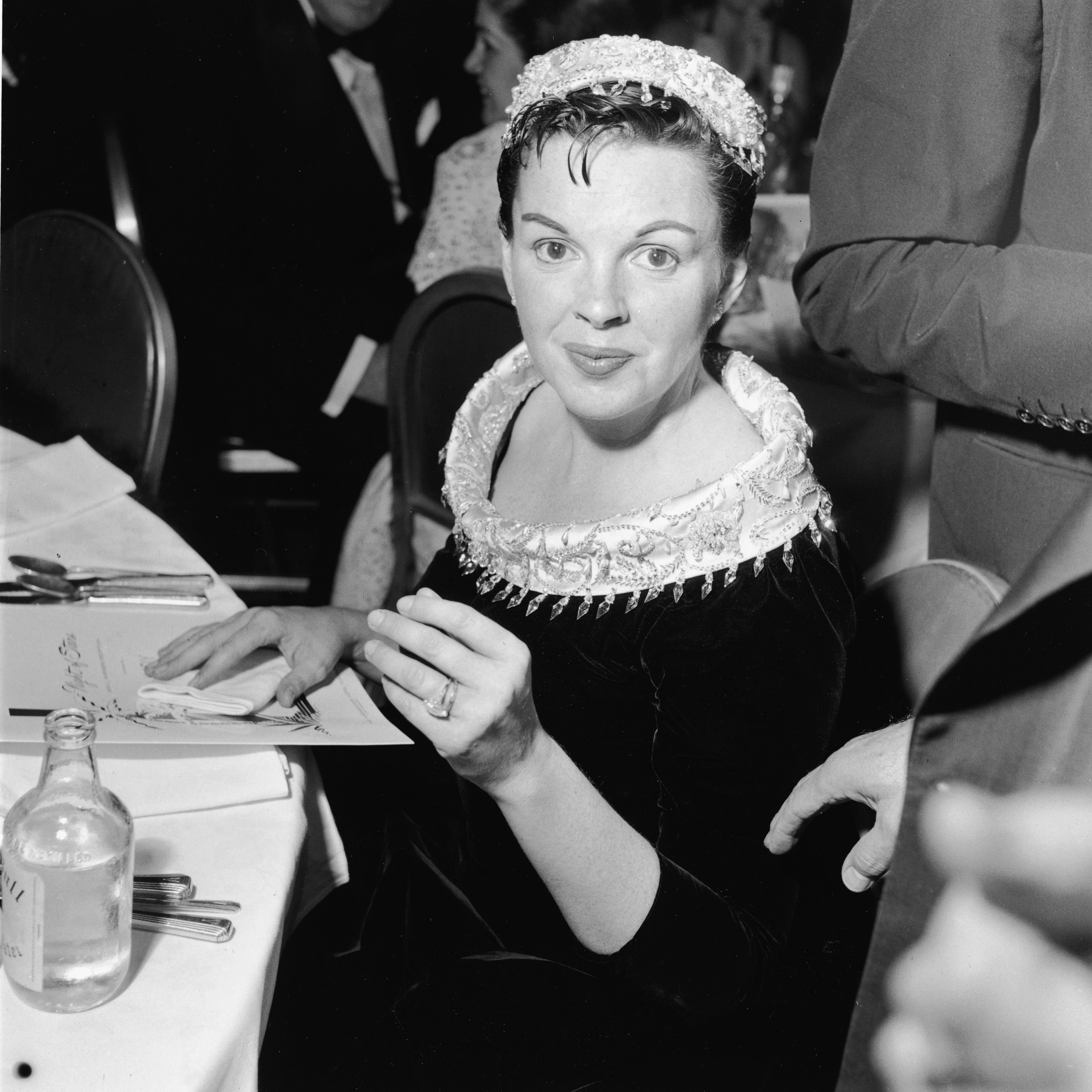 "Judy Garland (1922 - 1969) sits at a table at the premiere of the film ""A Star Is Born."" 