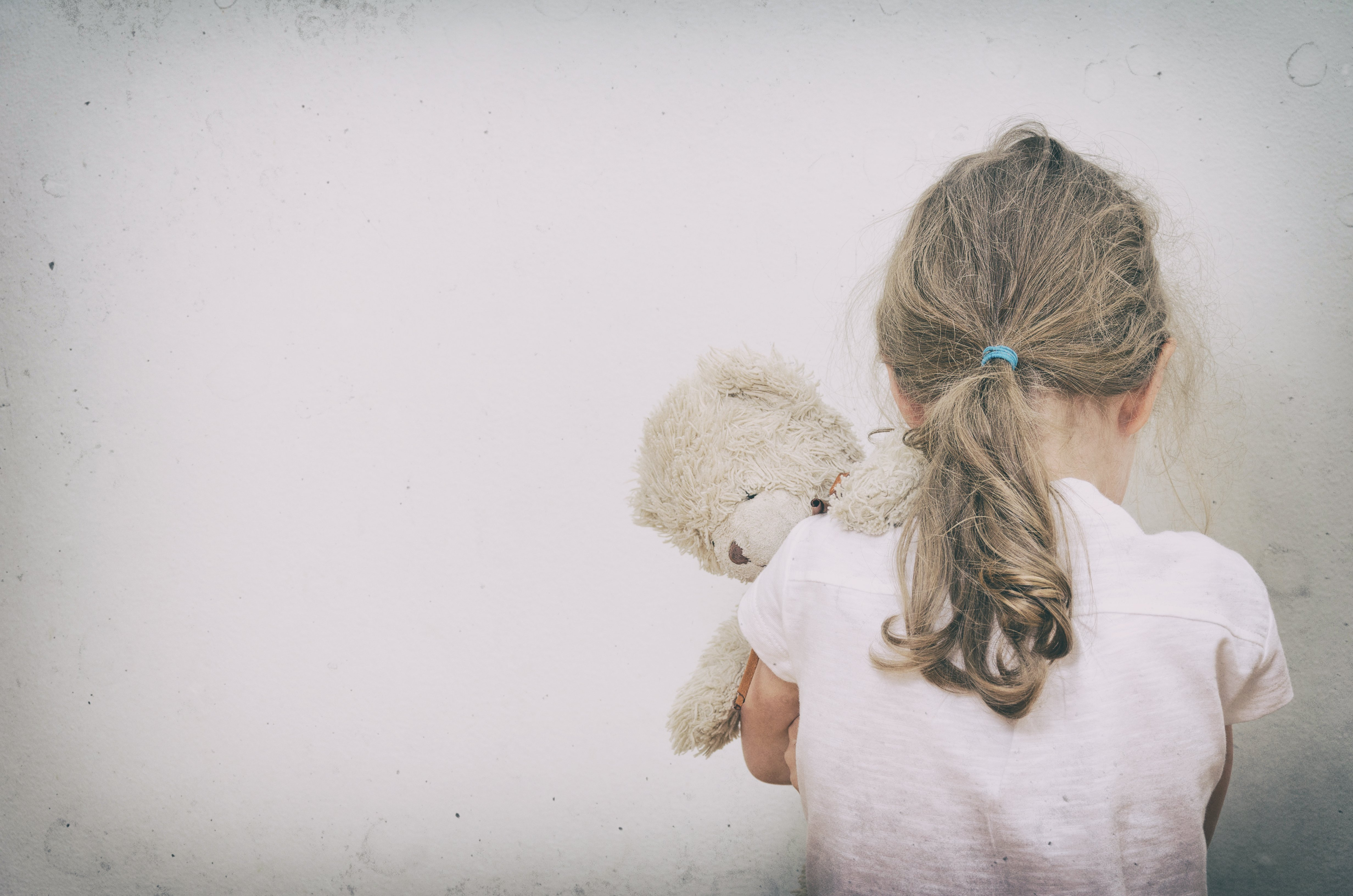 A sad little girl from the back holding her teddy bear. | Source: Shutterstock