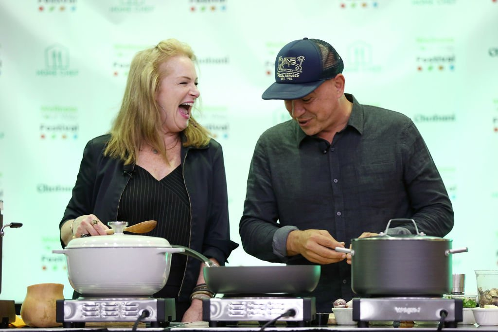 Michael Symon and Liz Symon participate in a cooking demo. | Source: Getty Images